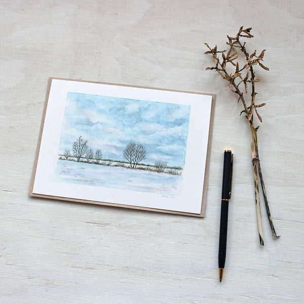 Note card featuring a watercolor painting of a tree-lined snowy field. Artist Kathleen Maunder.