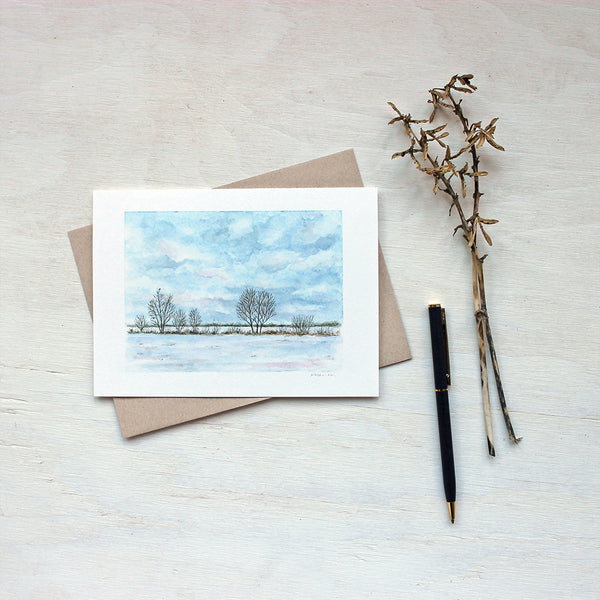 Note card featuring a watercolor painting of a cloudy sky, snowy field, a line of trees and a tiny bird. Artist Kathleen Maunder.