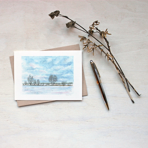 Note card featuring a watercolour painting of a cloudy sky, snowy field, a line of trees and a tiny bird. Artist Kathleen Maunder.