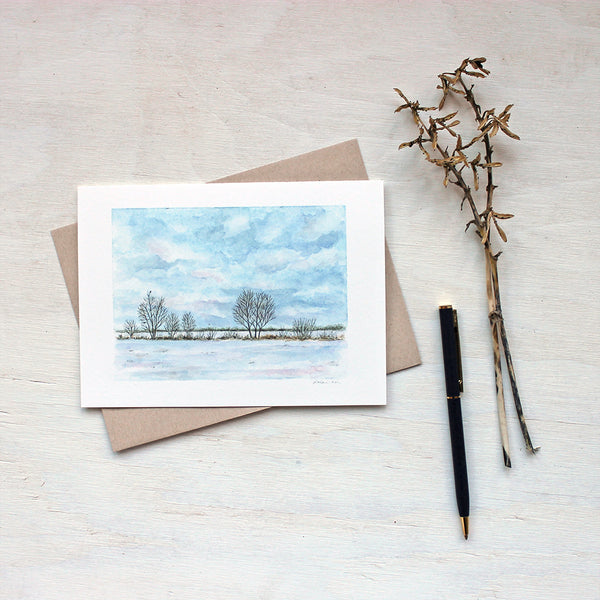 Note card featuring a watercolor painting of a snowy field, a line of trees and a tiny bird. Artist Kathleen Maunder.