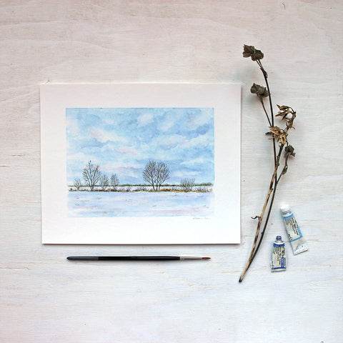 A watercolor art print featuring a wintry landscape including a rural field, trees and a tiny bird. Artist Kathleen Maunder.
