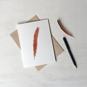 Note card featuring a watercolor painting of a female Northern cardinal's tail feather. Artist Kathleen Maunder.