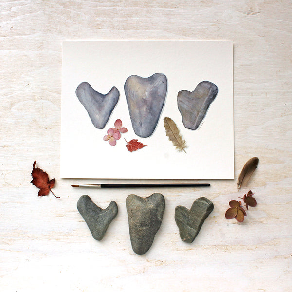 Watercolor print of heart rocks, hydrangea blossoms, a leaf and a feather / Artist Kathleen Maunder