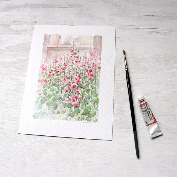 Side view of an art print featuring pink hollyhocks painted by watercolor artist Kathleen Maunder
