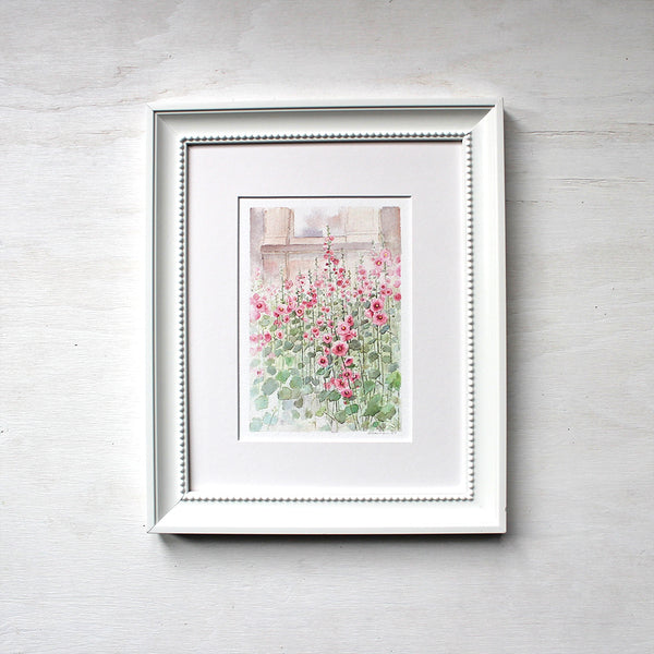 A 6 x 8 inch print of a watercolor painting of hollyhocks. Shown matted and framed. Artist Kathleen Maunder.