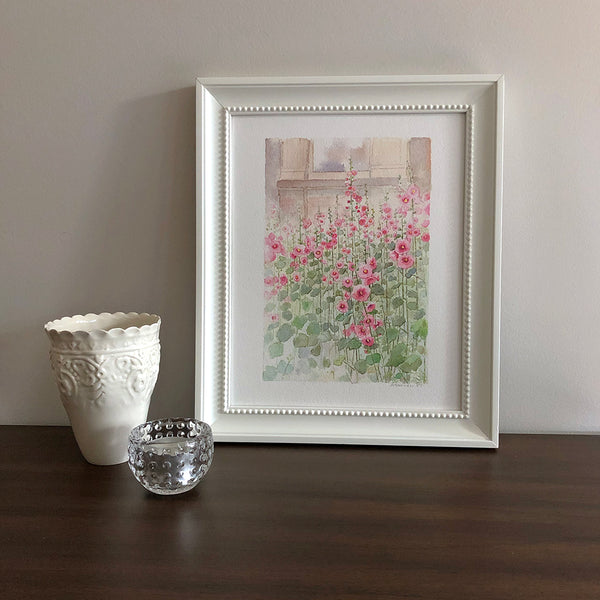 An 8 x 10 inch print of a watercolor painting of hollyhocks. Shown framed. Artist Kathleen Maunder.