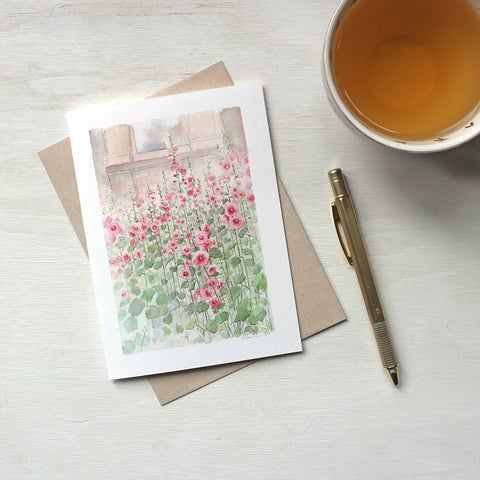 Note card featuring a watercolor painting of pink hollyhocks. Artist Kathleen Maunder.