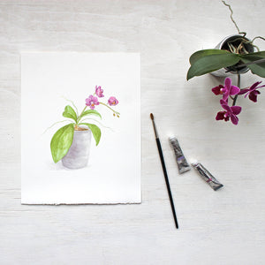 Watercolor painting of a tiny orchid plant with magenta-colored blossoms by artist Kathleen Maunder. Available as print.