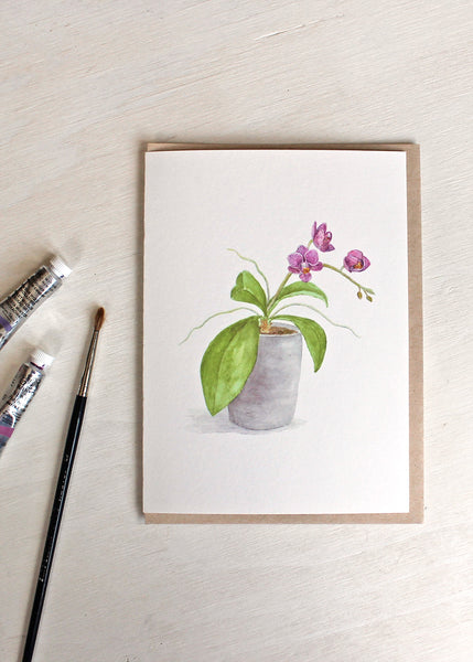 A blank note card featuring a watercolor painting of a pot of tiny purple orchids. Artist Kathleen Maunder.
