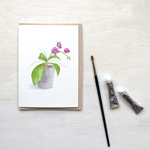 Note card featuring a watercolor painting of tiny magenta orchids. Artist Kathleen Maunder.