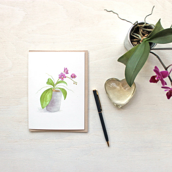 Note card featuring a watercolor painting of a pot of small purple orchids. Artist Kathleen Maunder.