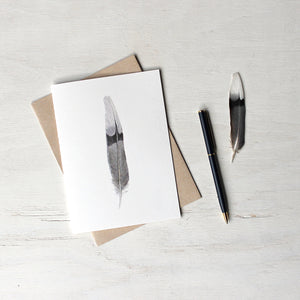 Note card featuring a watercolor painting of a black, gray and white mourning dove feather. Artist Kathleen Maunder.