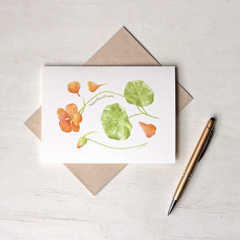 Note card featuring watercolour painting of orange nasturtium flower, petals, bud and leaves. Artist Kathleen Maunder.