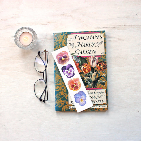 Bookmark featuring watercolor paintings of four pansies by artist Kathleen Maunder