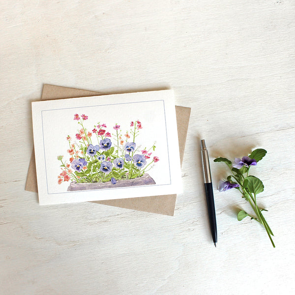 Note card featuring watercolor painting of purple-blue pansies, nemesia, diascia and euphorbia
