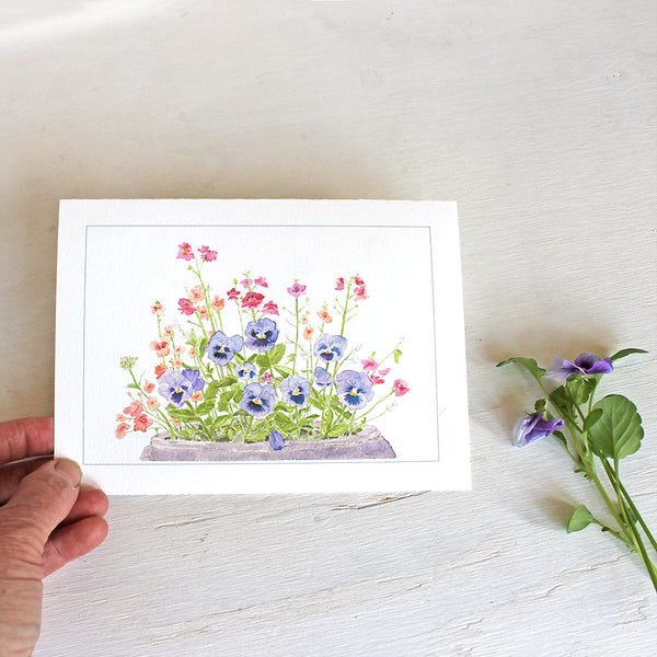 Note card featuring watercolor painting of purple-blue pansies, nemesia, diascia and euphorbia. Artist Kathleen Maunder.