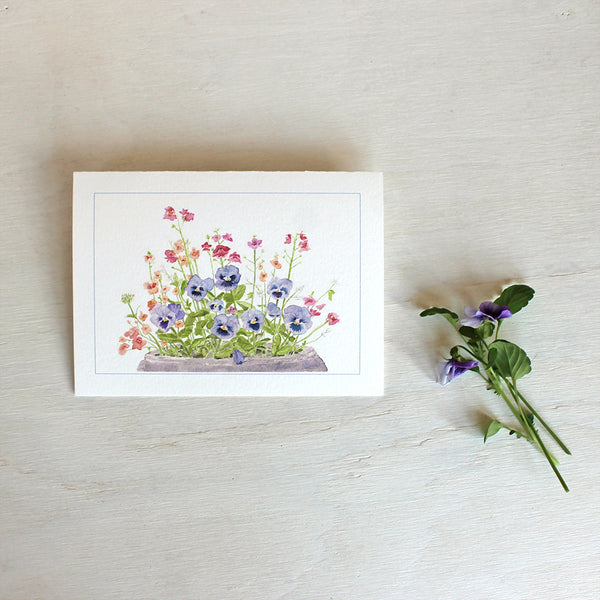 Purple blue pansies in a pot. Watercolour painting on a a note card by Kathleen Maunder