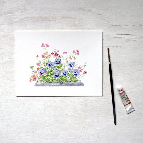 A print of a watercolor painting depicting a flower pot containing blue pansies, pink nemesia, coral diascia and white euphorbia. Artist Kathleen Maunder.