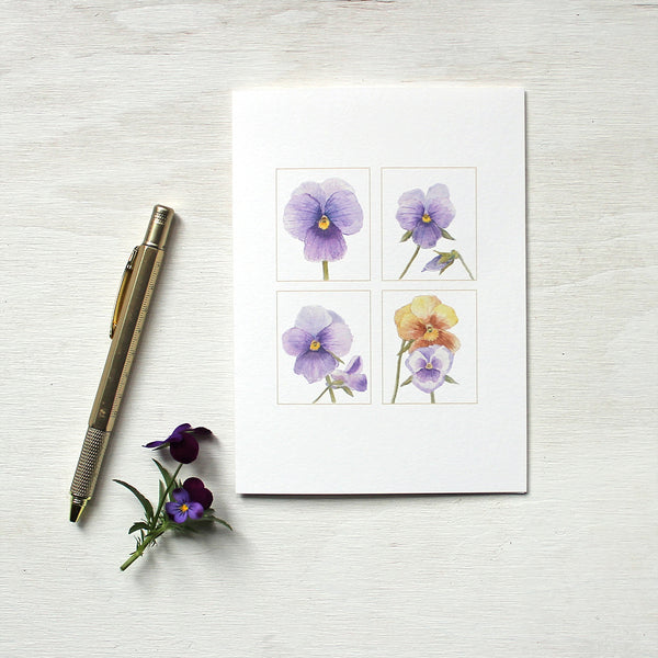 A note card featuring watercolour paintings of purple and gold pansies by artist Kathleen Maunder.