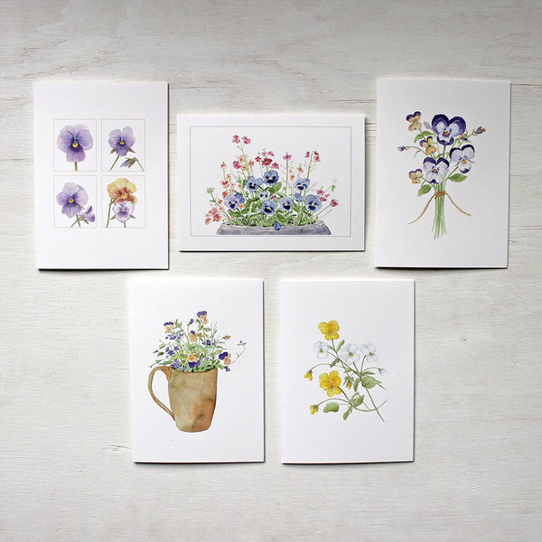 Five note cards depicting paintings of pansies and violas by watercolour artist Kathleen Maunder.