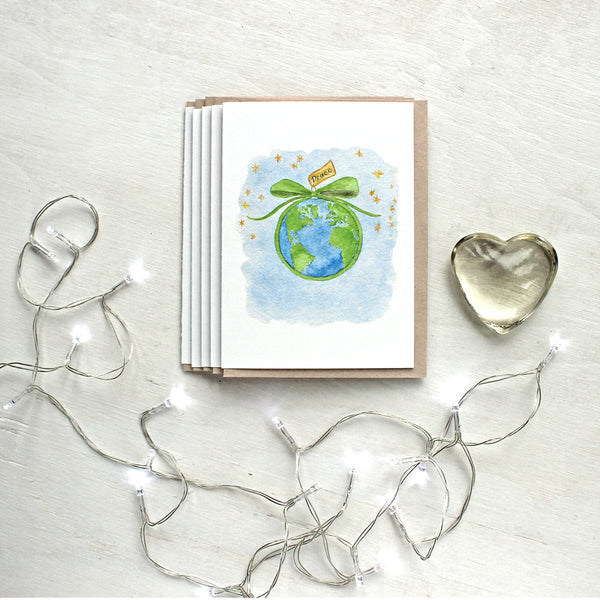 Set of Christmas cards with a watercolor painting by Kathleen Maunder of the earth tied with a green bow and a message of peace.