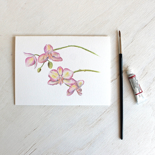 Note card featuring a watercolour painting of pink and yellow orchids. Artist Kathleen Maunder.