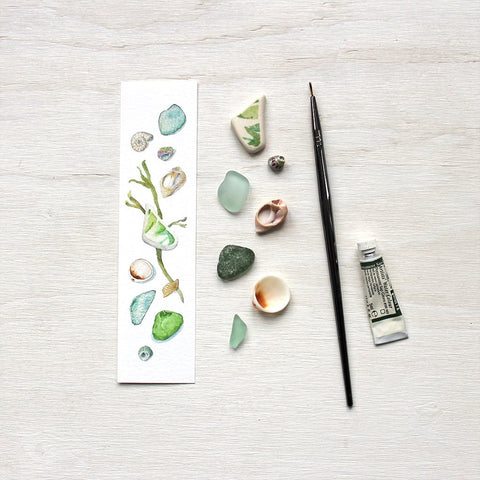 Paper bookmark with watercolor painting of sea finds (shells and beach glass)