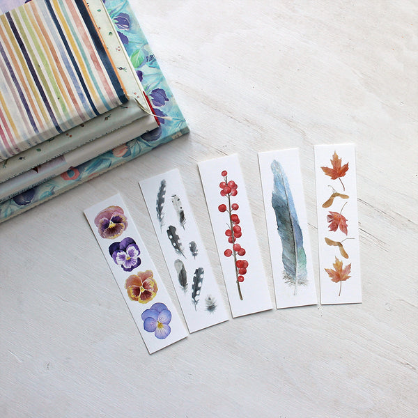 Set of five watercolor bookmarks by Kathleen Maunder. Set includes pansies, woodpecker feathers, winterberries, blue feather and maple leaves.