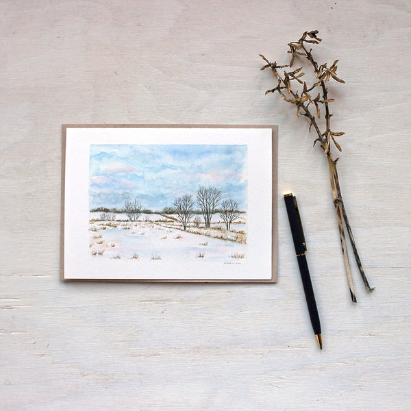 A note card featuring a watercolor painting of a winter landscape including snowy fields, trees and a cloudy sky. Artist Kathleen Maunder.