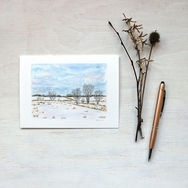 A note card featuring a watercolor painting of a winter landscape including snowy fields, trees, and a cloudy sky. Artist Kathleen Maunder.