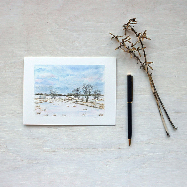 A blank note card featuring a watercolour painting of a snowy rural landscape. Artist Kathleen Maunder.