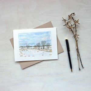 A blank note card featuring a landscape painting of snowy rural fields and a beautiful cloudy sky. Watercolor artist Kathleen Maunder.