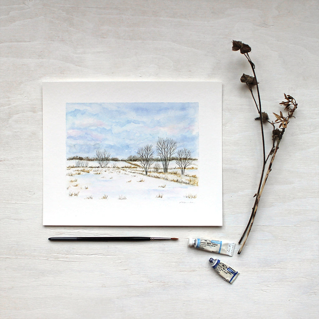 A print featuring a landscape painting in watercolor. Snowy fields, trees and blue wintry clouds. Artist Kathleen Maunder.