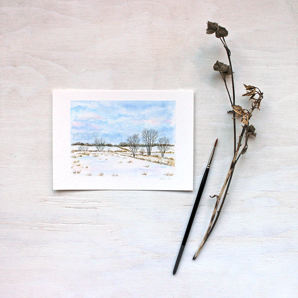 A print featuring a watercolor painting of a rural landscape: snowy fields, trees and blue wintry clouds. Artist Kathleen Maunder.