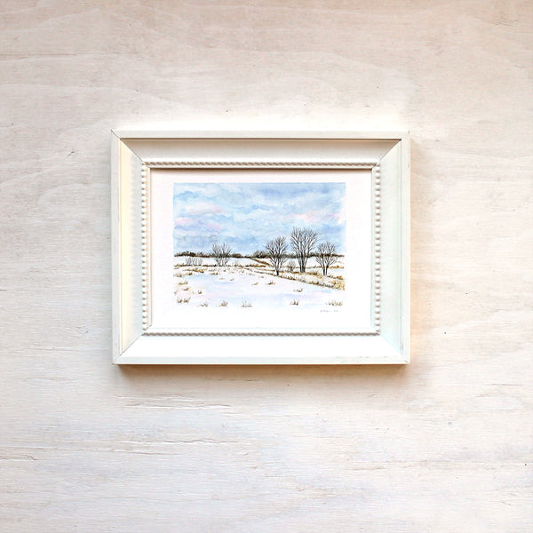 Framed print featuring a watercolor painting of snowy fields. Artist Kathleen Maunder.