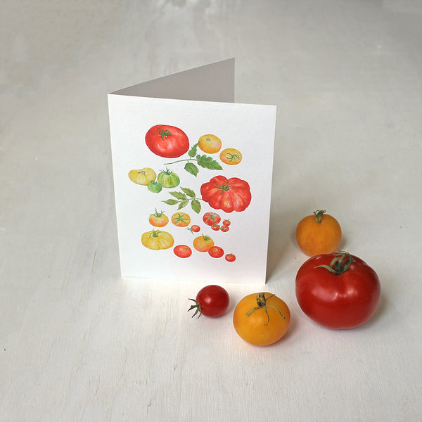 A note card depicting several kinds of red, yellow and green heirloom tomatoes by watercolour artist Kathleen Maunder.
