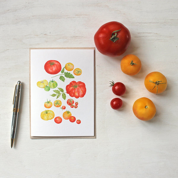 A watercolor note card with paintings of several kinds of red, yellow and green heirloom tomatoes by artist Kathleen Maunder.