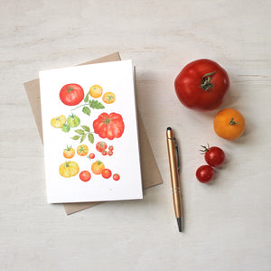A note card depicting several kinds of red, yellow and green heirloom tomatoes by watercolor artist Kathleen Maunder.