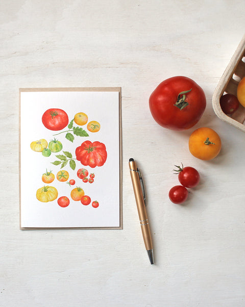 A blank note card featuring a watercolor painting of several types of red, yellow and green heirloom garden tomatoes. Artist Kathleen Maunder.