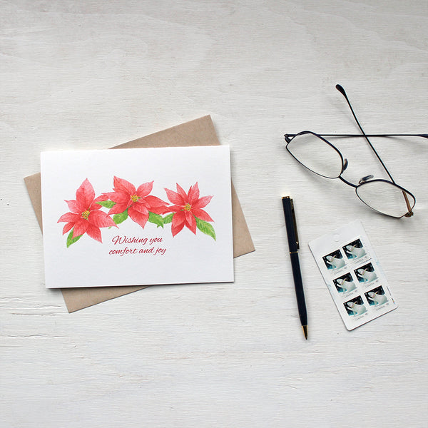 Holiday greeting card featuring three red poinsettia blooms by watercolor artist Kathleen Maunder.