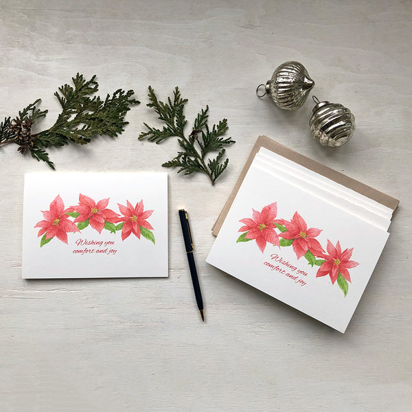 Set of Christmas cards featuring red and green poinsettia blooms painted in watercolor. Artist Kathleen Maunder.