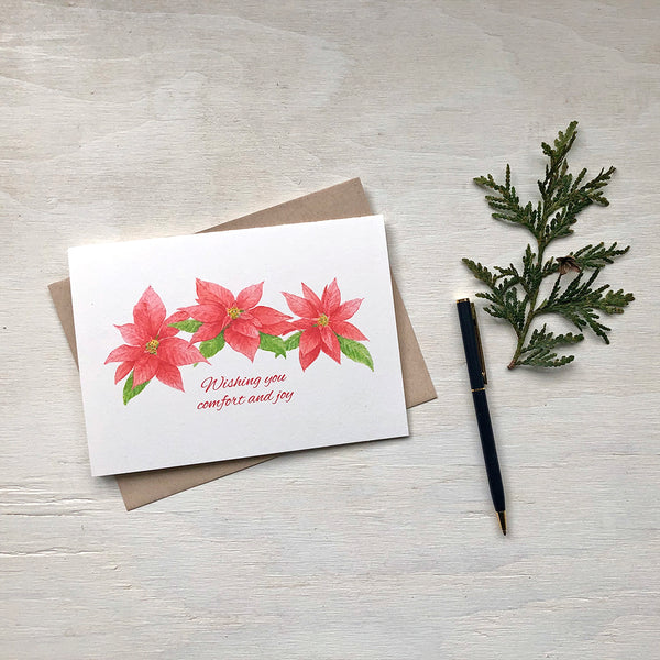 Christmas Card featuring three red and green poinsettia blooms painted in watercolour by artist Kathleen Maunder