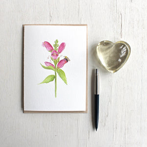 Note card featuring watercolor painting of pink turtlehead flower and a bee. Artist Kathleen Maunder.