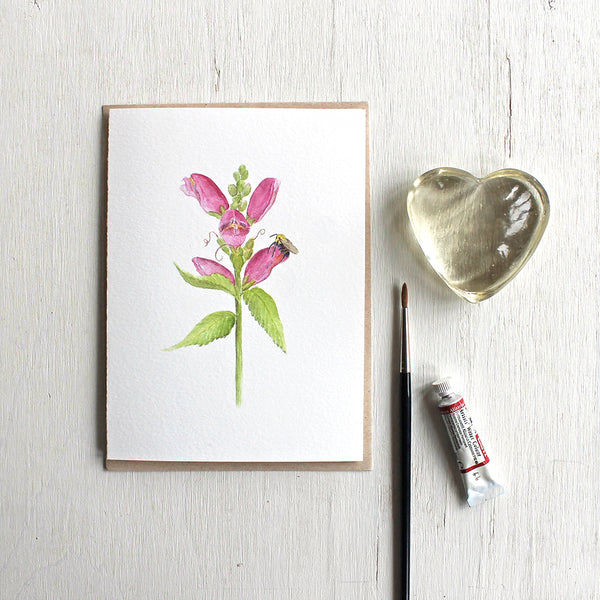 Note card with watercolor painting of pink turtlehead flower and a bee. Artist Kathleen Maunder.