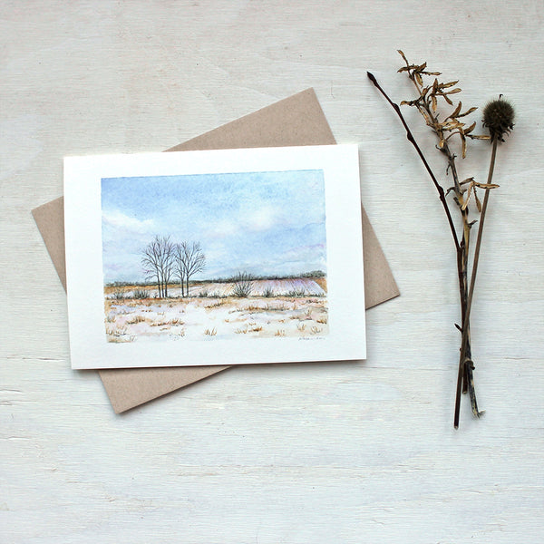 A note card featuring a watercolor painting of a winter landscape including a snowy field, trees, blue sky and fluffy clouds.