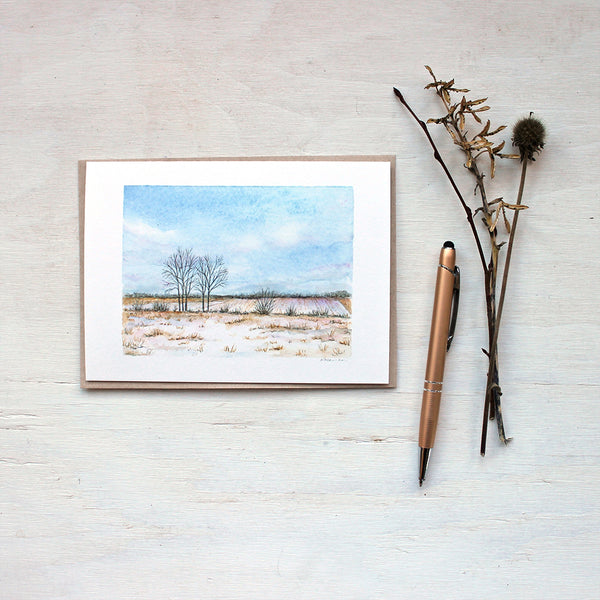 A blank note card featuring a watercolor painting of a snowy rural field and beautiful cloudy sky. Artist Kathleen Maunder.