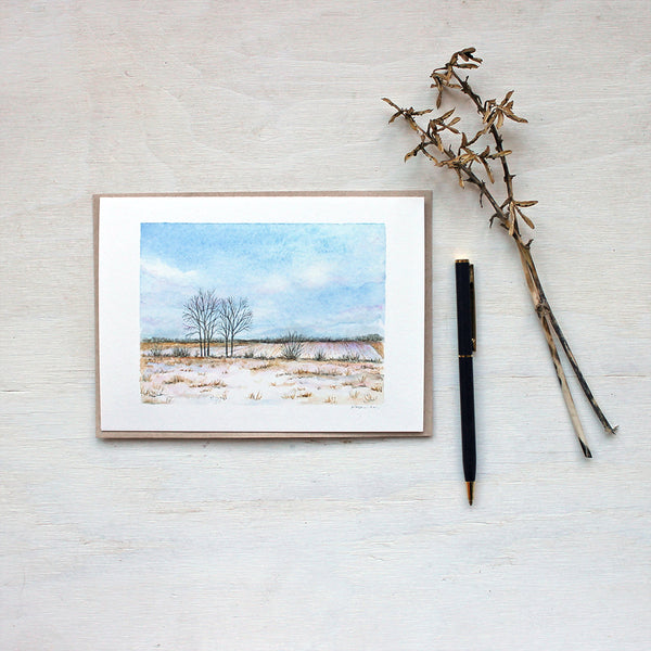 Note card featuring a watercolor painting of a snowy field and cumulus clouds. Artist Kathleen Maunder.