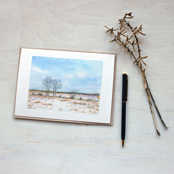 A blank note card featuring a watercolor painting of a snowy rural landscape. Artist Kathleen Maunder.