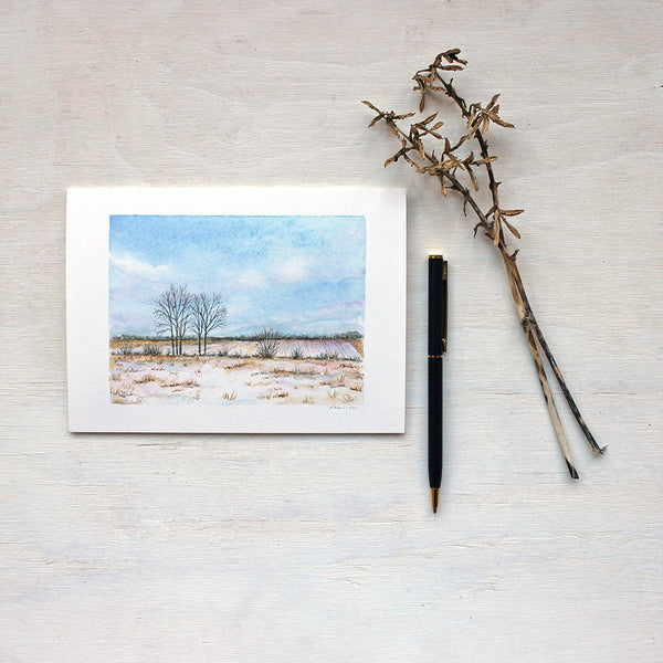 Note card featuring a watercolor painting of a snowy field and soft fluffy clouds. Artist Kathleen Maunder.
