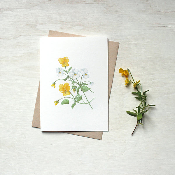 Note card featuring a watercolour painting of yellow and white violas. Accompanied by kraft envelope. Artist Kathleen Maunder.